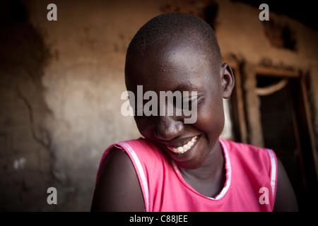 Shy teenage girl laughing - Amuria, Uganda, East Africa. - Stock Photo
