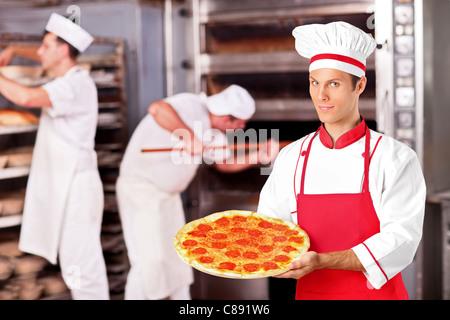 A male baker holding freshly baked pizza in bakery - Stock Photo