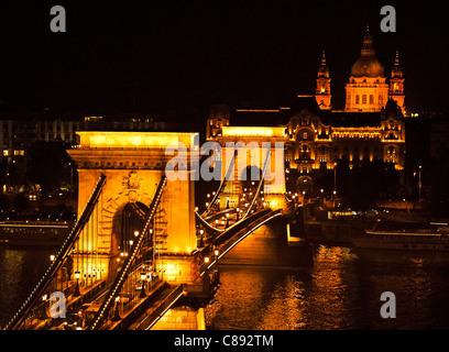View of Chain Bridge and St. Stephen's Basilica at night - Budapest, Hungary - Stock Photo
