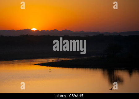 Sunrise over Aravalli Mountain Range at Chattra Sagar reservoir and bird reserve at Nimaj, Rajasthan, Northern India - Stock Photo