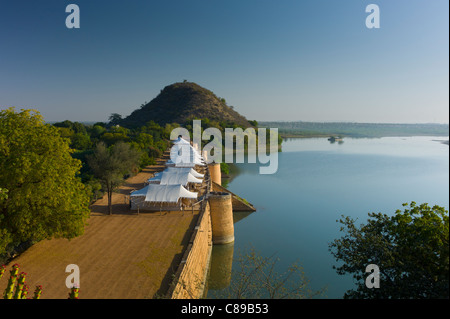 Chhatra Sagar reservoir and luxury tented camp oasis in the desert at Nimaj, Rajasthan, Northern India - Stock Photo