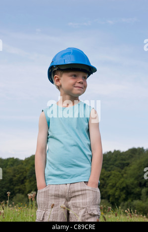 Germany, North Rhine-Westphalia, Hennef, Boy with construction worker helmet standing in meadow - Stock Photo