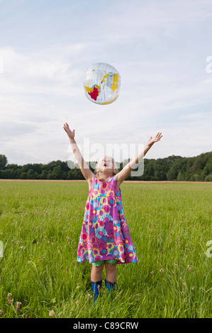 Germany, North Rhine-Westphalia, Hennef, Girl throwing beach ball globe in meadow - Stock Photo