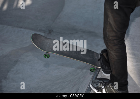 Germany, North-Rhine Westphalia, Muenster, Skateboader dropping his leg in skatebowl at public skate park - Stock Photo
