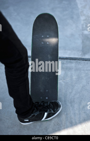 Germany, North-Rhine Westphalia, Muenster, Skateboader standing at skatebowl at public skate park - Stock Photo