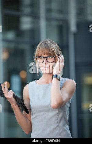 Germany, Bavaria, Munich, Young businesswoman with spectacles using mobile phone - Stock Photo