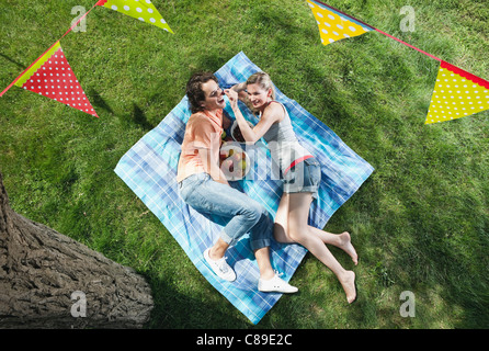 Italy, Tuscany, Young couple lying on picnic blanket with food and flag line hanging above - Stock Photo