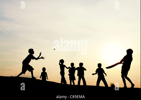 Silhouette of young Indian boys playing french cricket at sunset in India - Stock Photo