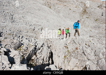 Austria, Kleinwalsertal, Group of people hiking on rocky mountain trail - Stock Photo