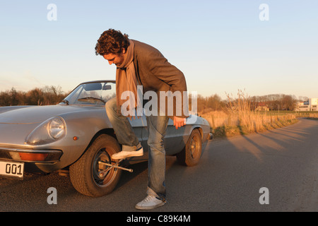 Germany, Hamburg, Man changing tyre of classic cabriolet car - Stock Photo