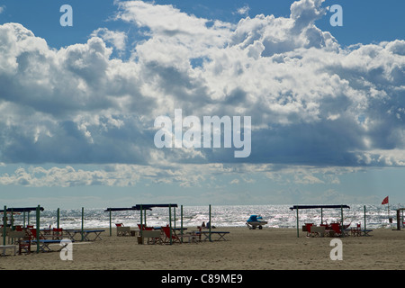Italy, Forte dei Marmi, View of sandy beach with blue sky and white dense clouds - Stock Photo