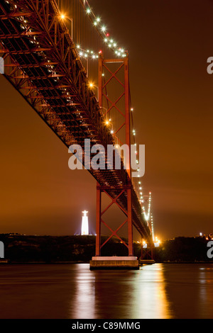 Europe, Portugal, Lisbon, View of suspension bridge with river Tagus at night - Stock Photo