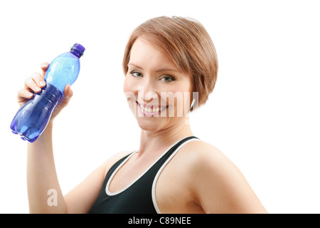Tired but happy sportive woman drinking water from blue bottle after training isolated on white - Stock Photo