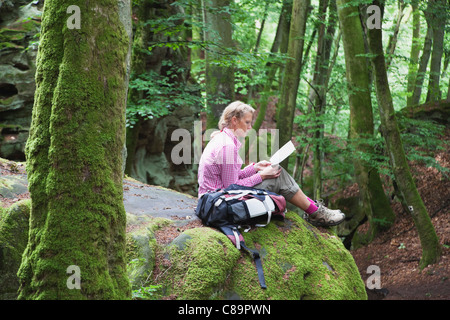 Germany Rhineland-Palatinate South Eifel Nature Park Woman hiker sitting on bunter rock formations at beech tree - Stock Photo