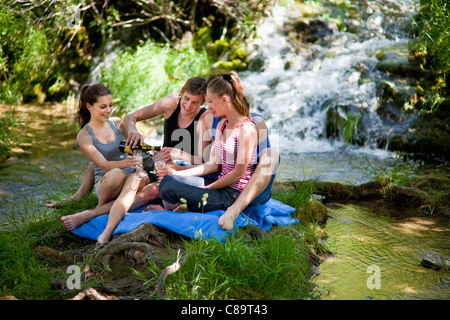 Italy, Tuscany, Friends with champagne sitting on grass and having picnic - Stock Photo