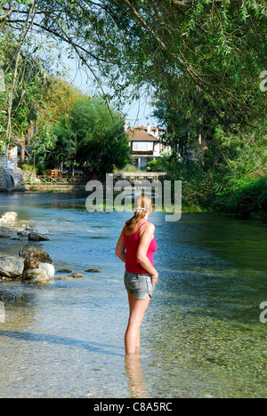 A young woman standing in a shallow river. 2011. - Stock Photo