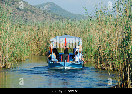 AKYAKA, TURKEY. A small pleasure boat taking holidaymakers along the Azmak river in the Gokova conservation area. - Stock Photo