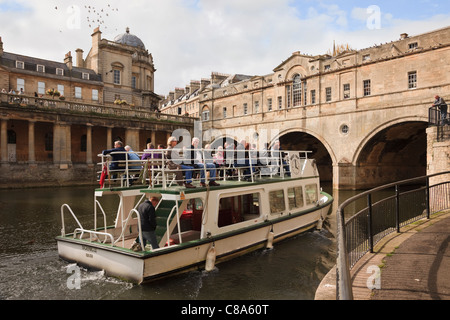 Tourists on a sightseeing cruise boat trip on the River Avon by Pulteney Bridge. Bath, Somerset, England, UK Britain - Stock Photo