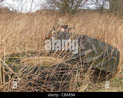 A hunter crouched down behind old tractor tyres in camouflage clothing in the long grass holding a rifle and watching - Stock Photo