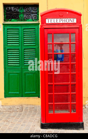 A traditional red English phone in front of yellow wall and a green door, Malta - Stock Photo