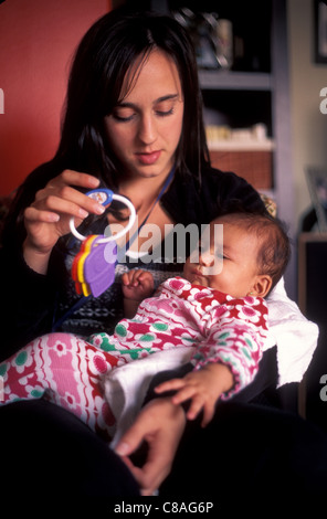 A 5 month old Hispanic baby chews her hands (while teething). - Stock Photo