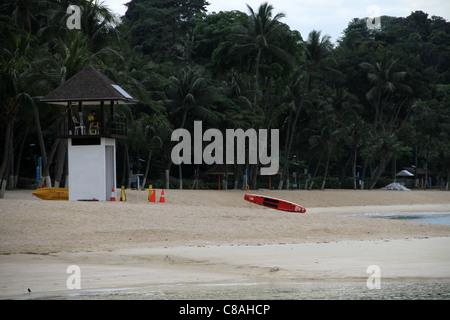 A lifeguard on Palawan Beach gazes out across the south China.  Sentosa Island, Singapore. - Stock Photo
