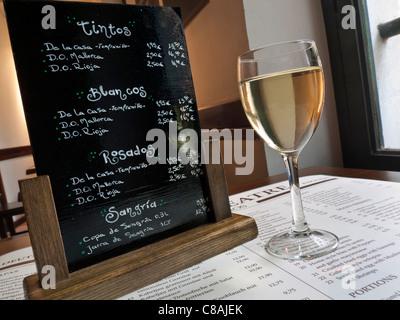 BLACKBOARD WINE LIST TABLE Glass of white Mallorcan wine, restaurant menu and Spanish blackboard wine list on table, - Stock Photo