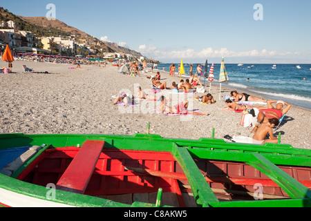 Tourists sunbathing, Letojanni Beach, Letojanni, Sicily, Italy - Stock Photo