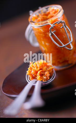 Jar and spoonful of pumpkin and chestnut chutney - Stock Photo