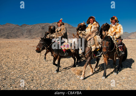Kazakh eagle hunters and their golden eagles in the Altai Region of Bayan-Ölgii in Western Mongolia - Stock Photo
