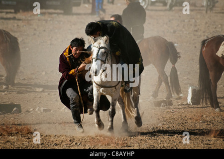 Kazakhs playing kokbar, a traditional sport  played on horseback, at the Eagle Festival in western Mongolia - Stock Photo
