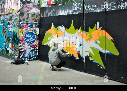 Graffitti artist at work on South Bank, London wearing a pair of headphones - Stock Photo