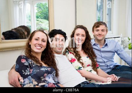 Portrait of friends sitting on sofa - Stock Photo