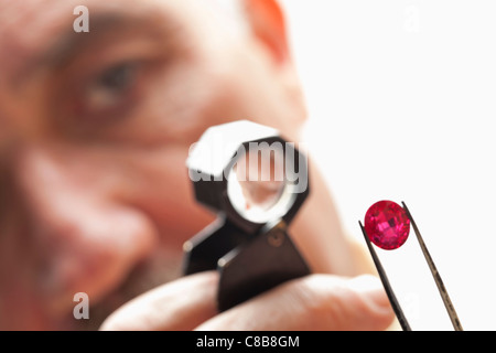 Close up of gemstone with jeweler looking through magnifying glass - Stock Photo