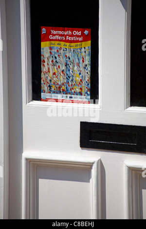 poster advertising the Yarmouth Old Gaffers Festival stuck in glass panel of door in Yarmouth, Isle of Wight - Stock Photo