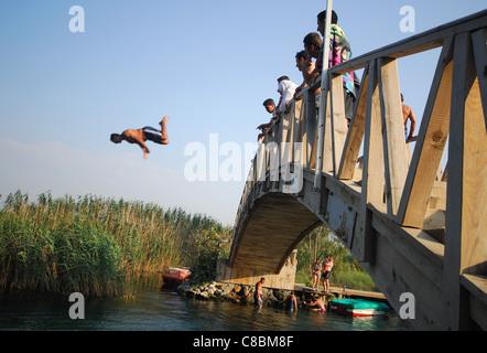 AKYAKA, TURKEY. A man diving off a wooden bridge into the Azmak river. 2011. - Stock Photo