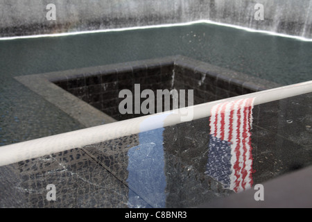 American Flag reflecting in a pool at the National September 11 Memorial - Stock Photo