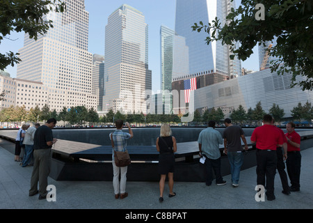 Visitors stand by the South Pool at the National September 11 Memorial in New York City. - Stock Photo