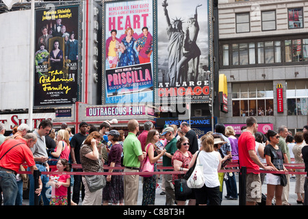 People stand in line to purchase discount theater tickets at the TKTS booth in Duffy Square in Times Square, New - Stock Photo