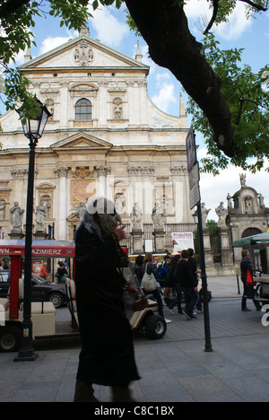 Street artist in front of Saints Peter and Paul Church in Cracow with one of the most beautiful baroque elevation - Stock Photo