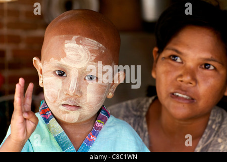 Unidentified mother and daughter wearing traditional Thanaka cream in Nyaung-U, Myanmar - Stock Photo