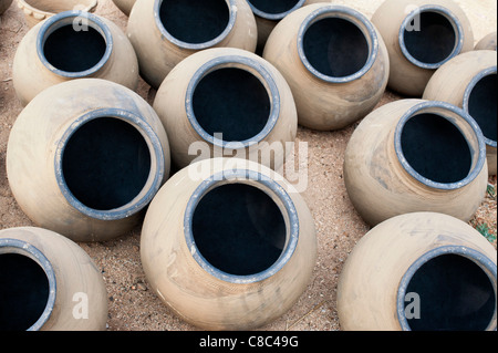 Hand made indian water pots drying in the sun before firing. Andhra Pradesh, India - Stock Photo