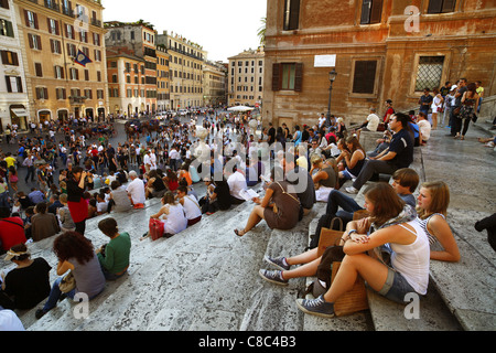 Tourists sat on the Spanish Steps above the Piazza di Spagna in Rome, Italy. - Stock Photo