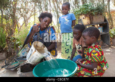 A woman and her children draw water from a well in Mongu, Zambia, Southern Africa. - Stock Photo