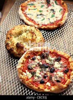 Selection of pizzas on a grill - Stock Photo