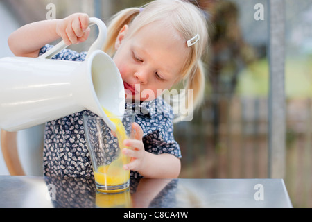 Toddler girl pouring glass of juice - Stock Photo