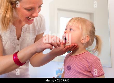 Mother brushing toddler daughter's teeth - Stock Photo