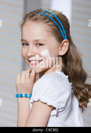 Girl with heart-shaped moisturizer - Stock Photo