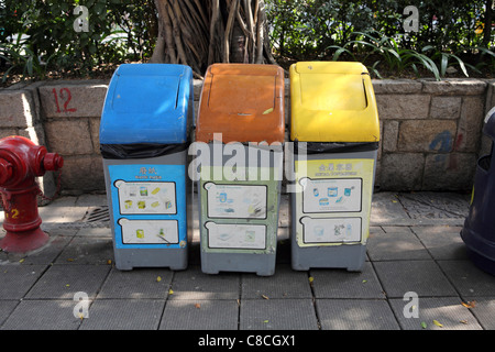 Color coded recycling bins on pavement in Kowloon, Hong Kong China. Recycling is fast becoming part of civic duty - Stock Photo