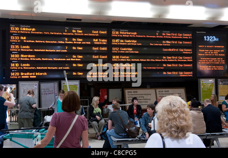 Passengers looking at a passenger information board at Kings Cross railway Station in London. - Stock Photo